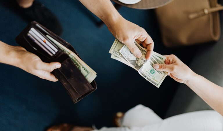 A man takes money from his wallet and hands it to a woman