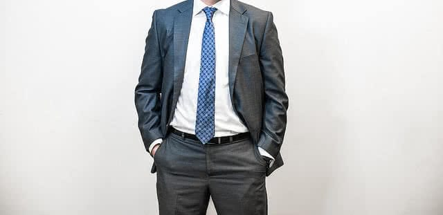 Cropped photo of a man standing with hands in pockets, man wears a grey suit with white shirt and blue tie. Image for article Confessions of a Punter, NZ Pleasures.
