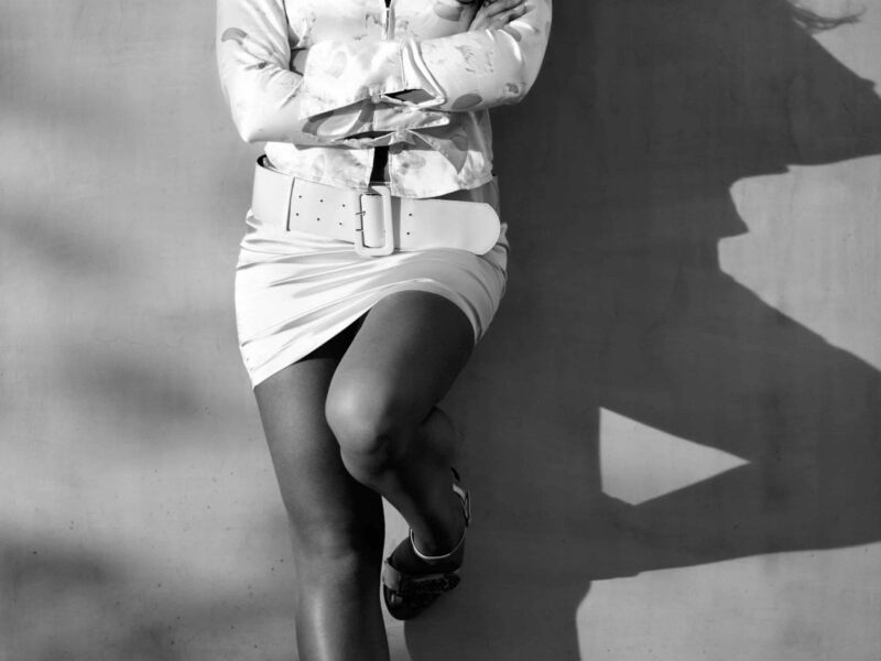 Black and white photo of a woman leaning against a concrete wall, one foot up against wall, arms crossed. Woman wears a white mini dress and jacket, heels and has long dark hair, looks like waiting for client. NZ Pleasures.