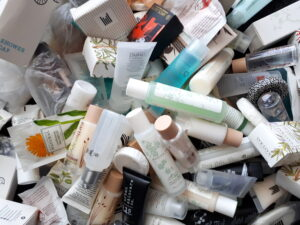 A pile of hotel toiletries, shampoos, soaps and conditioners.