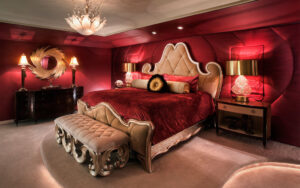 A boudoir, decked put with red velvet, chandeliers and a high top bed head.
