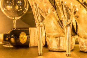 A yellow tinged image showing a pair of stiletto heels, and behind them a bottle of wine laying down next to a wine glass.