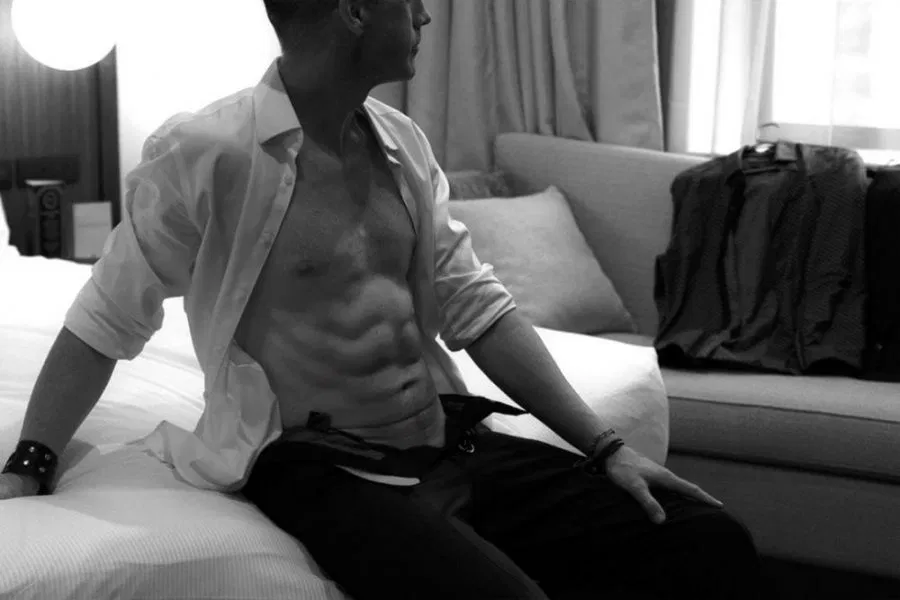 Black and white photo of Harley Brixton sitting on the end of a bed, one hand to his side, the other resting on his lower thigh. Harley wears a undone tailored shirt that is rolled up to his elbows and shows his 6 pack. Harvey's pants are undone at the top.