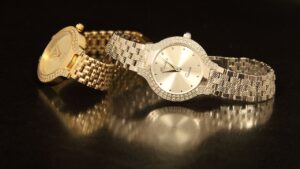 A pair of watches, one gold, one silver, both encrusted with diamonds around the watch face.