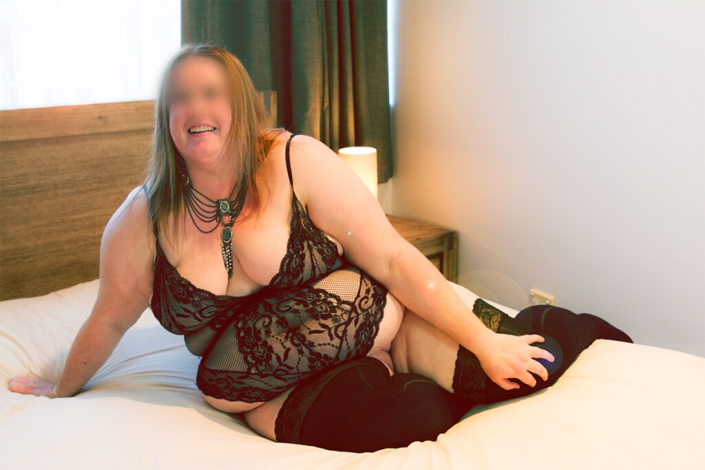 Vanessa sitting on a bed, leaning on one hand to the side, knees bent, other hand resting on knee. Vanessa wears a black bodysuit, black thigh high stockings and has long light brown hair. Image for article 7 Questions you always wanted to ask a BBW Escort. NZ Pleasures.