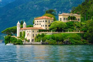 A small Italian town nested on the edge of a lake. The buildings are cream with orange rooves and surrounded by trees.