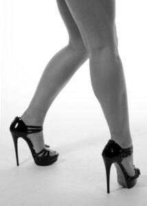 Black and white image of a woman's legs in black strappy heels.
