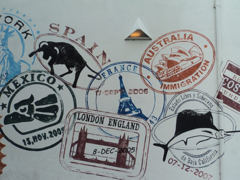 A collection of passport stamps from Spain, France, Australia, Mexico, New York and London, stamped onto a wall. Image for article Migrant Sex Workers - NZPC Interview. NZ Pleasures.