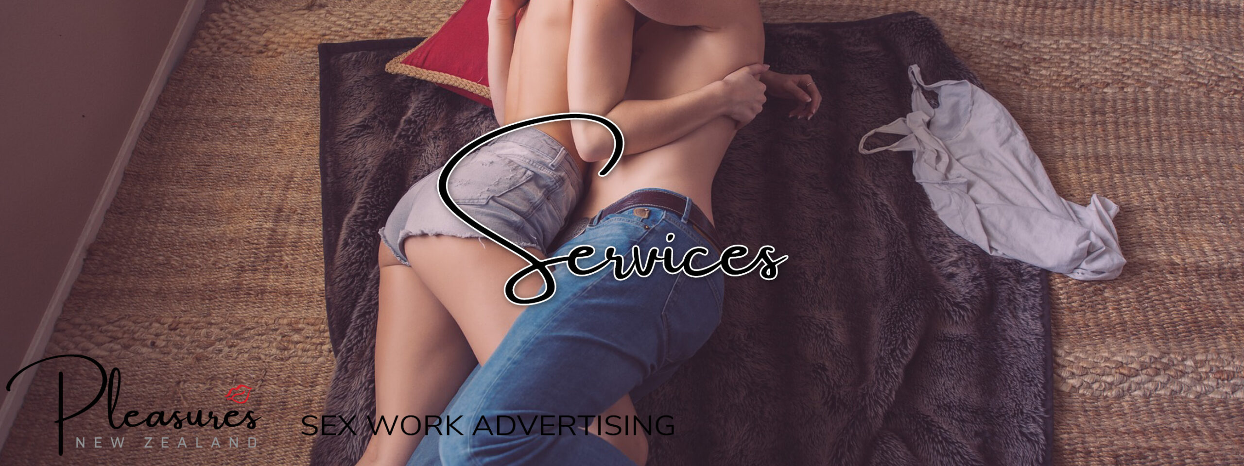 A man and a woman lying on a blanket on the floor, embracing each other, legs entwined, both topless. Sew Work Advertising Services Banner. NZ Pleasures.
