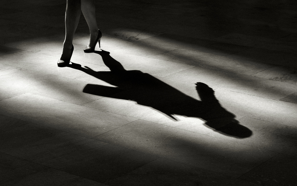 Black and white photo of a woman's shadow on the ground, only her legs in the photo, wearing high heels. Image for article Are you high class? NZ Pleasures.