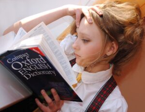 A young blonde hair woman reads the dictionary