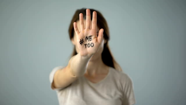 A woman holds her right hand up to the camera. Written on her palm is #MeToo