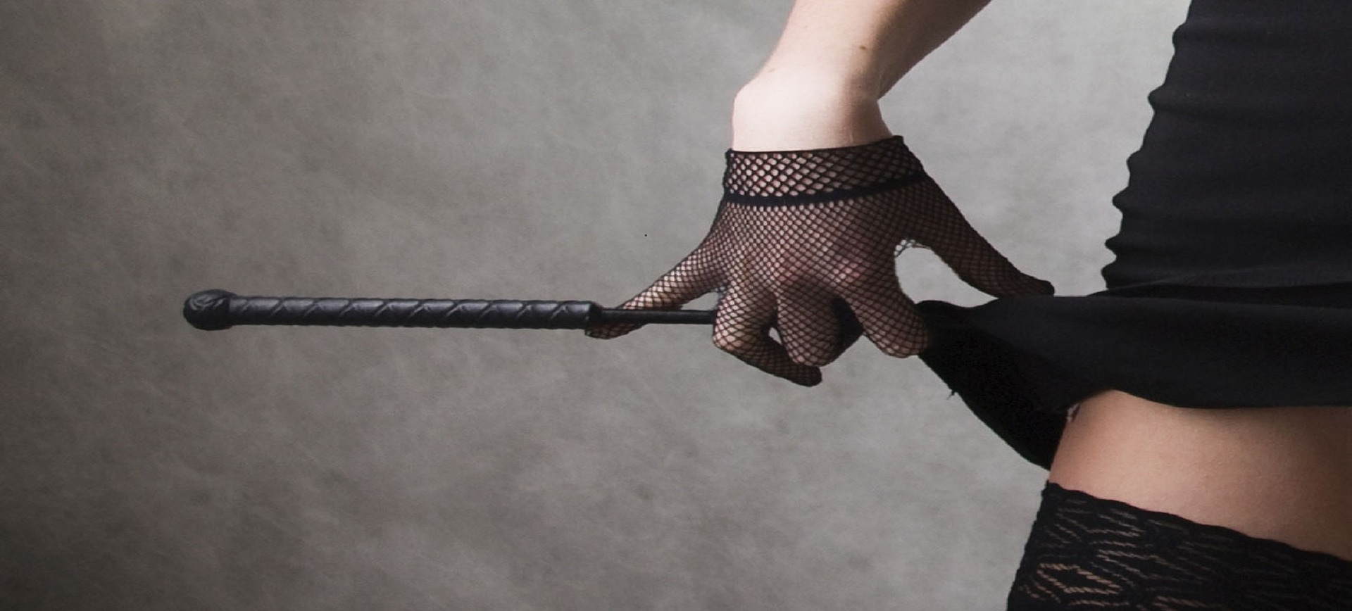 Photo of a crop held with a mesh gloved hand of which the finger is pulling up the side of a woman's black dress. Image for article Spanking with Mistress Joysin. NZ Pleasures.