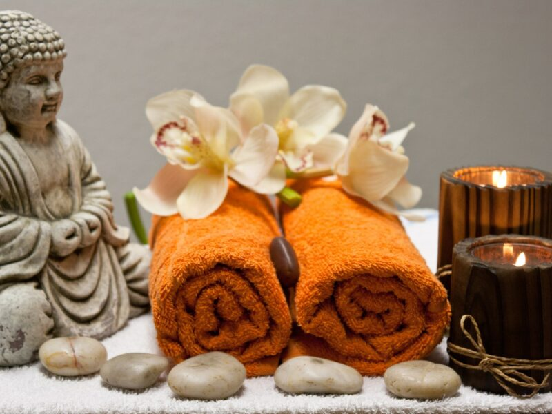 Two rolled up orange towels sitting next to a ceramic buddha, surrounded by stones, with two candles and two orchards. Image for article A retreat with no spa? NZ Pleasures.