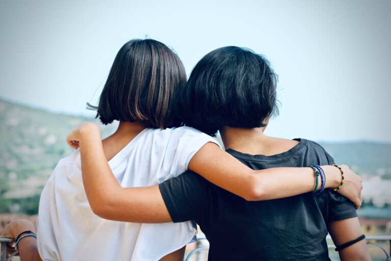 Two women with black hair embrace each other while facing away from the camera