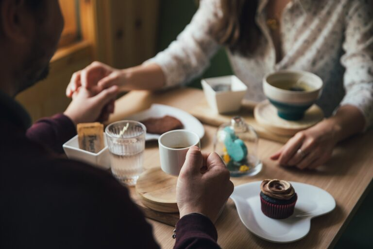 A dating couple sit at a cafe table and hold hands while drinking a hot drink and eating sweets.
