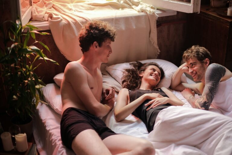 Two young men and a women lay between them on a bed